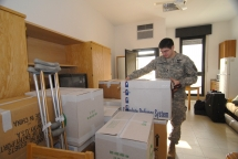 Sgt. Justin Varnes sets about unloading the boxes containing all his belongings, as he moves into one of the new single rooms in the WTU barracks at Vicenza, Italy.