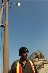 A concerned local citizen stands watch near a checkpoint in Arab Jabour, Iraq, Dec. 27, 2007. Street lights, a recent addition to the area, have improved the security climate. Photo by Sgt. Luis Delgadillo, USA