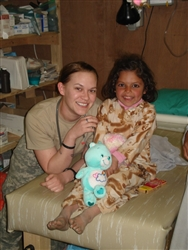 Shameera, an Afghan girl receiving medical care at Forward Operating Base Kalagush, Afghanistan, smiles with Army medic Pfc. Lauren Knickerbocker, Charlie