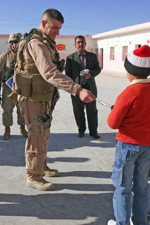"Captain Brian Von Kraus, the commander of Headquarters and Support Company, 1st Battalion, 1st Marine Regiment, Regimental Combat Team 6, hands an American written letter to an Iraqi student here during the second phase of ""Operation Iraqi Pen Pal,"" which is a letter exchange program bridging the gap between the young students of the local Iraqi schools here, and students of Boston and Maine public schools in the United States. The letters come from all over Boston and even from some schools in Maine, which include post cards and different photos showing America and its way of life, said Von Kraus."