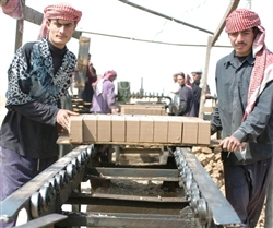 Workers at the Narhwan Brick Factory Complex move bricks from the cutter to carts pulled by donkeys March 25, 2008. The complex is home to 167 businesses, employs 15,000 Iraqis and produces nearly 4 million bricks per day. Photo by Sgt. 1st Class Scott Maynard, USA